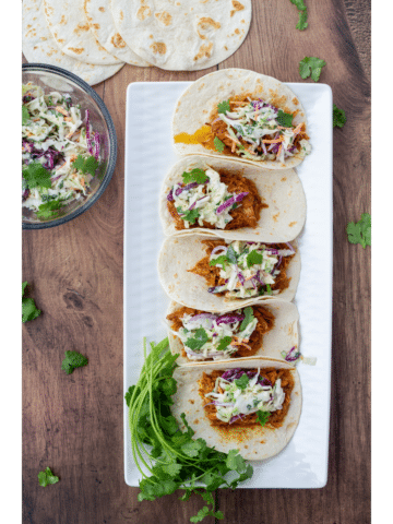 BBQ chicken tacos on a white plate and a dark wood background