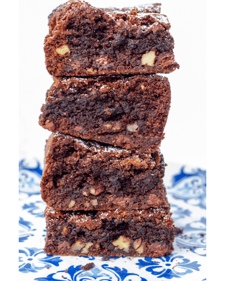 four brownies stacked high on a blue plate