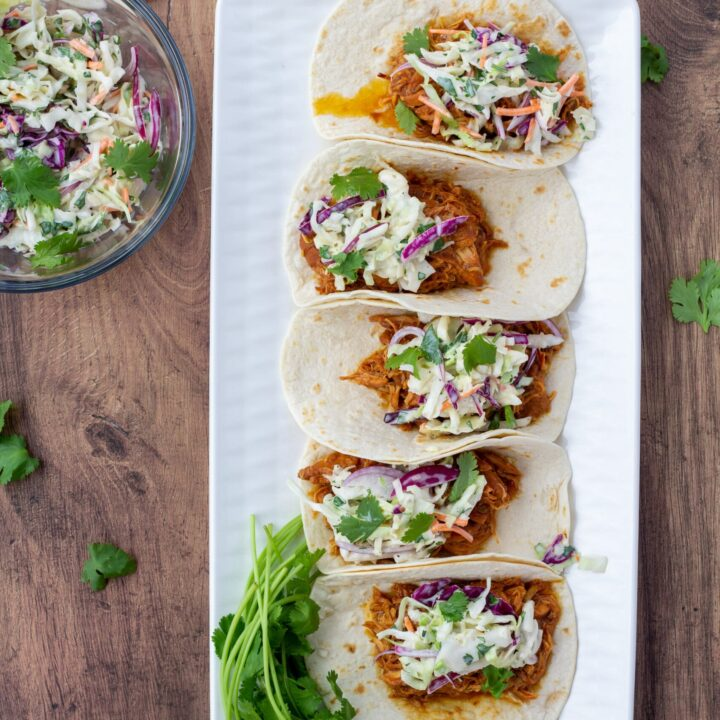 chicken tacos on a white plate and a wood background
