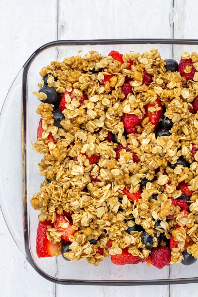 fruit crisp with oat topping on a white background