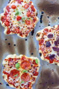three waffle iron pizzas, individual, on a white background