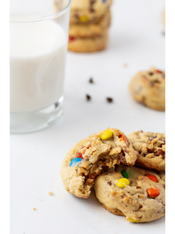 chocolate chip cookies on a white background with a glass of milk in the background