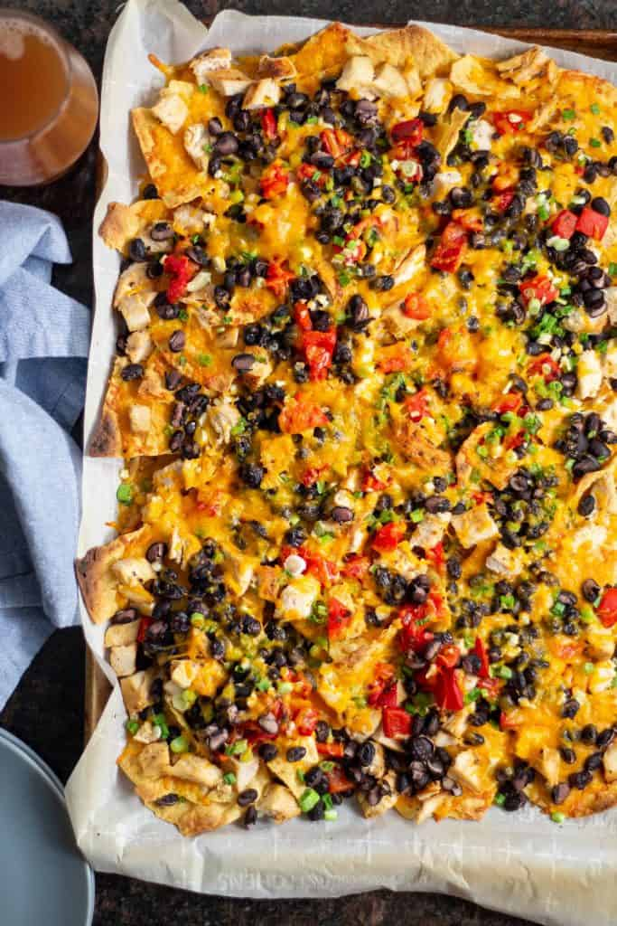 chicken nachos next to a blue napkin, plates, and a beer