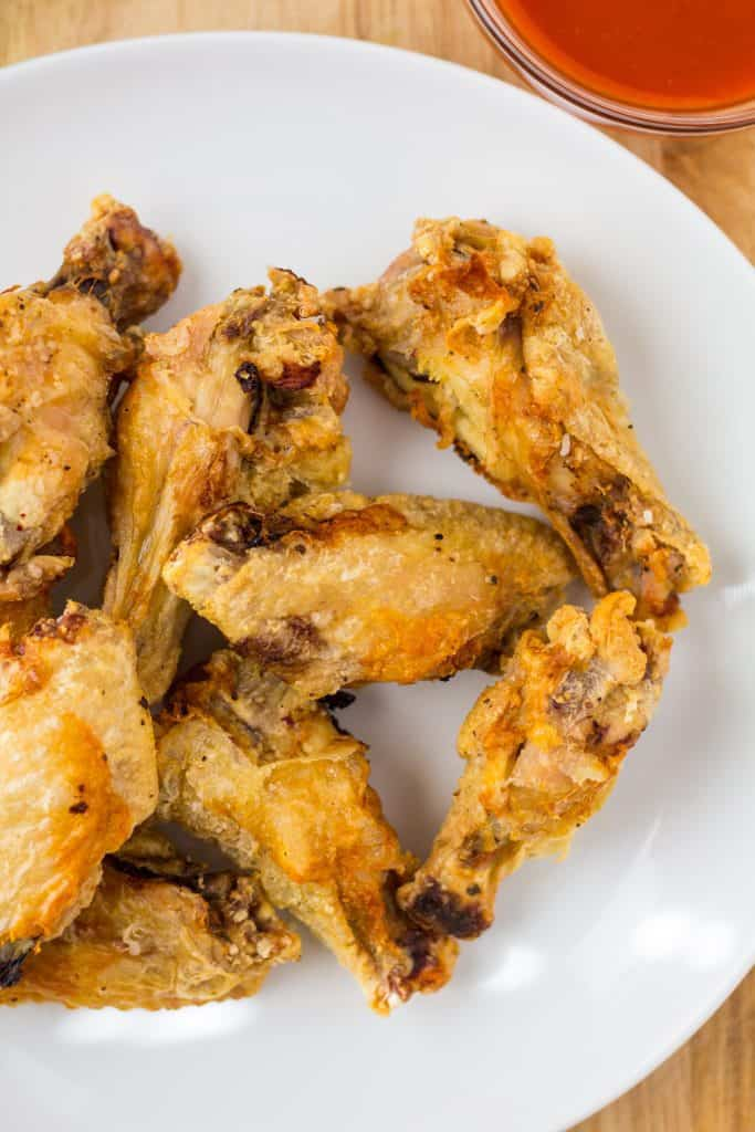 air fried chicken wings on a white plate with sauce on the sides