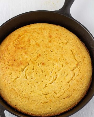 cornbread in a cast iron skillet on a white background