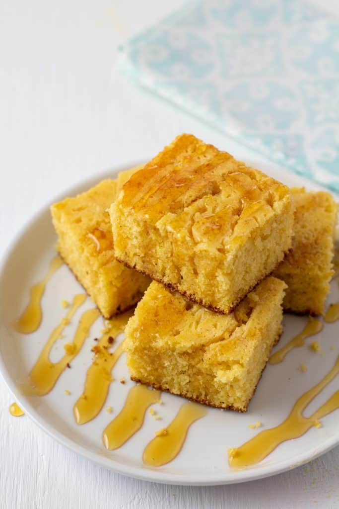 skillet cornbread drizzled in honey on a white plate