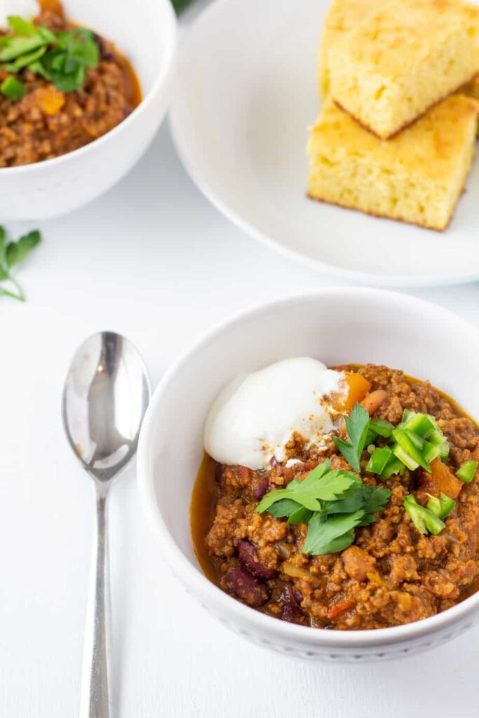 pumpkin chili in a white bowl with a spoon on the side.