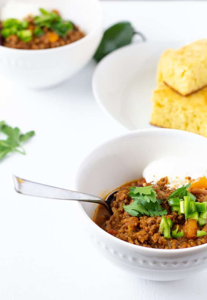 chili in a white bowl on a white background with a spoon.