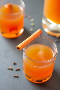 Apple cider in a clear glass on a black background with a cinnamon stick on top.