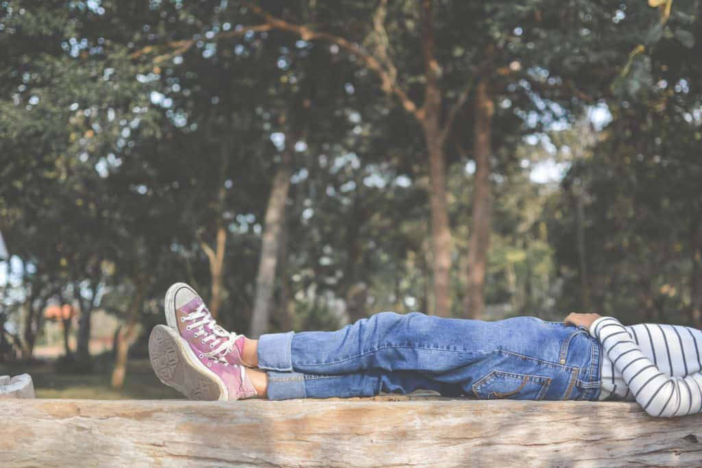 a woman laying down on a wooden fence while spending time at home
