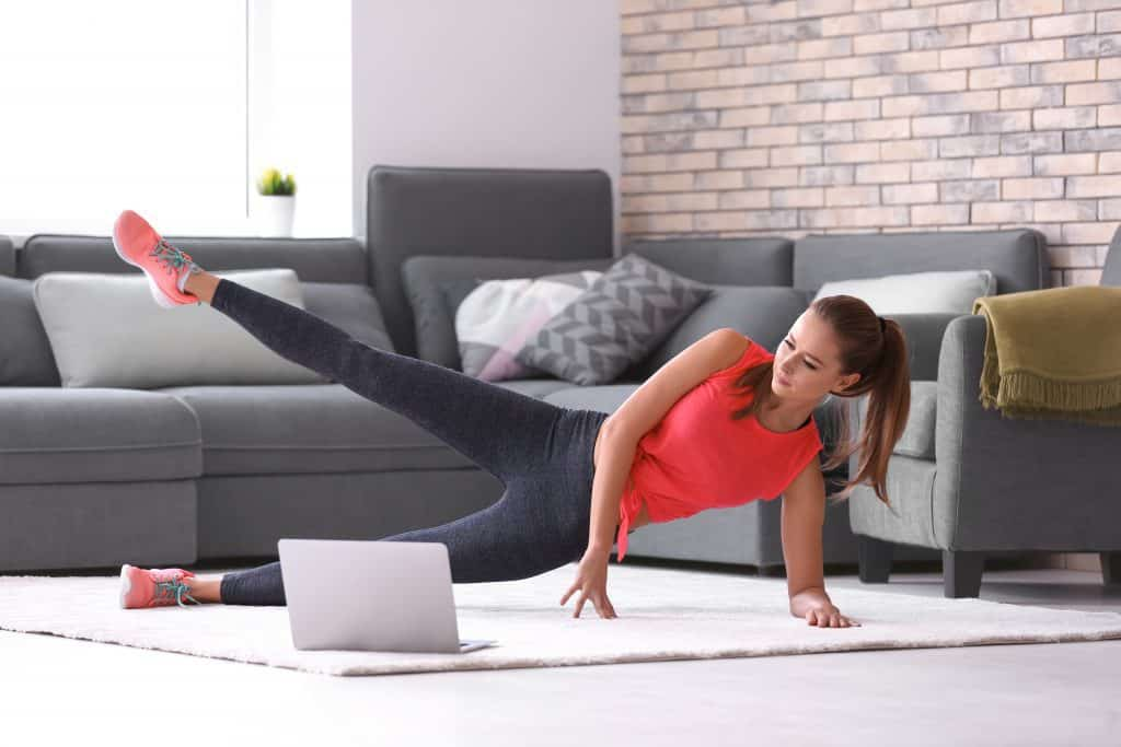 A woman exercising on the floor with a computer while spending time at home