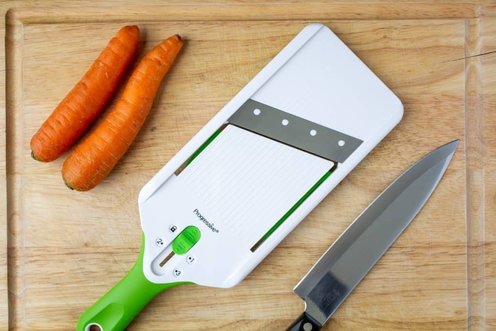 mandoline, carrots, chef knife, on cutting board