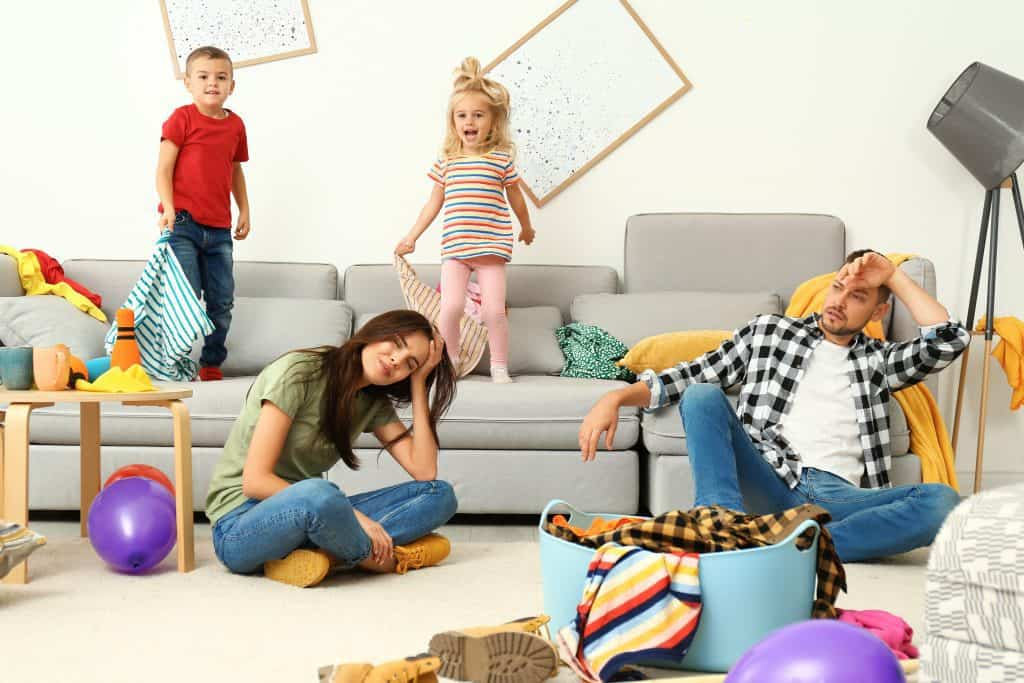 exhausted parents sitting on the floor in front of the couch while kids jump on it in a messy room