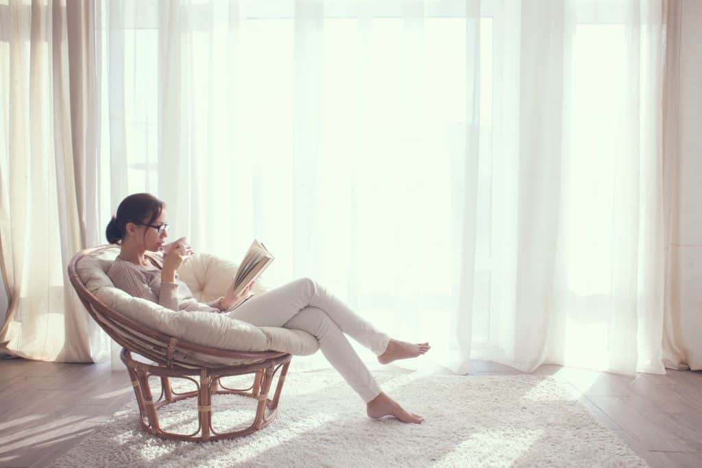 a woman reading in a white cushion chair while spending time at home