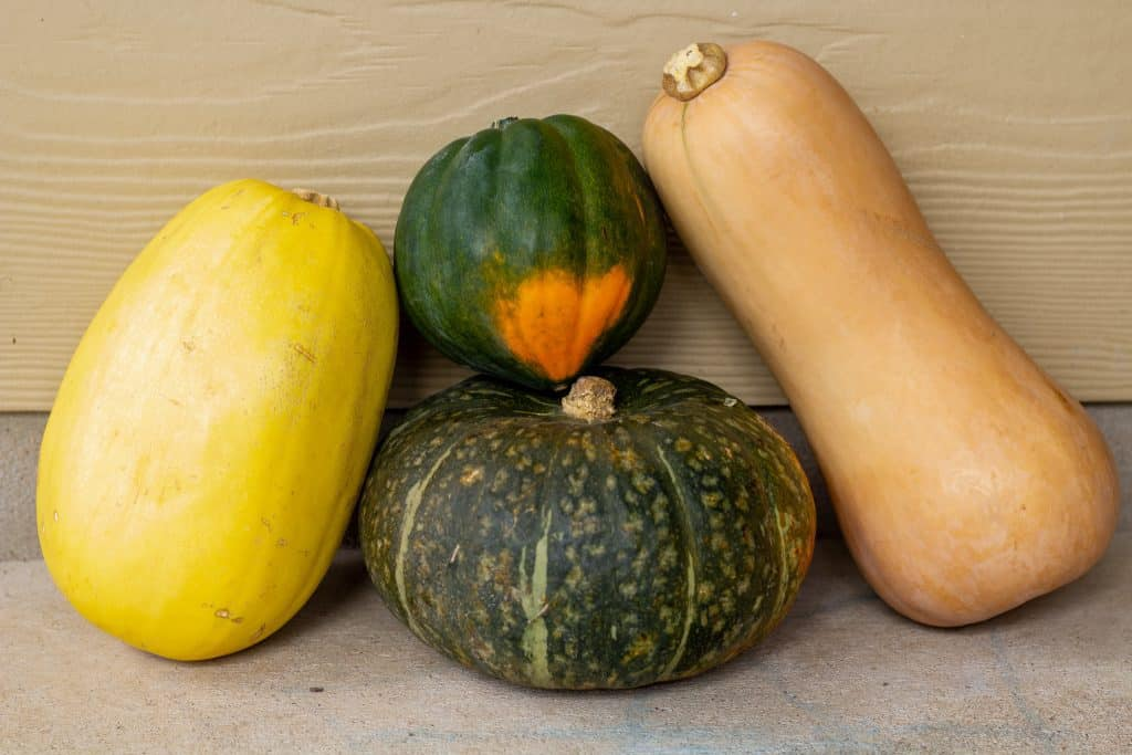 squashes stacked on top of each other with a tan background