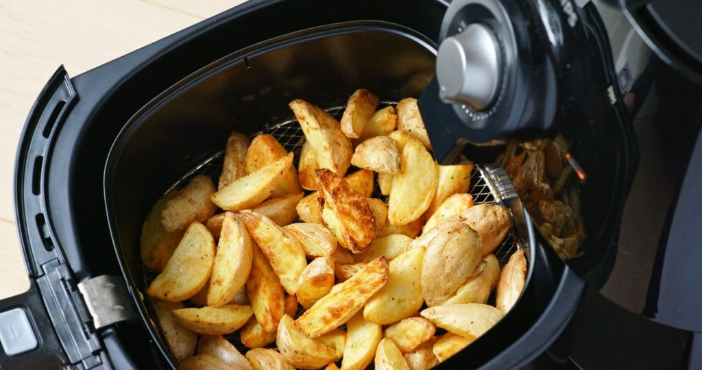 toasted potato wedges in the basket of an air fryer