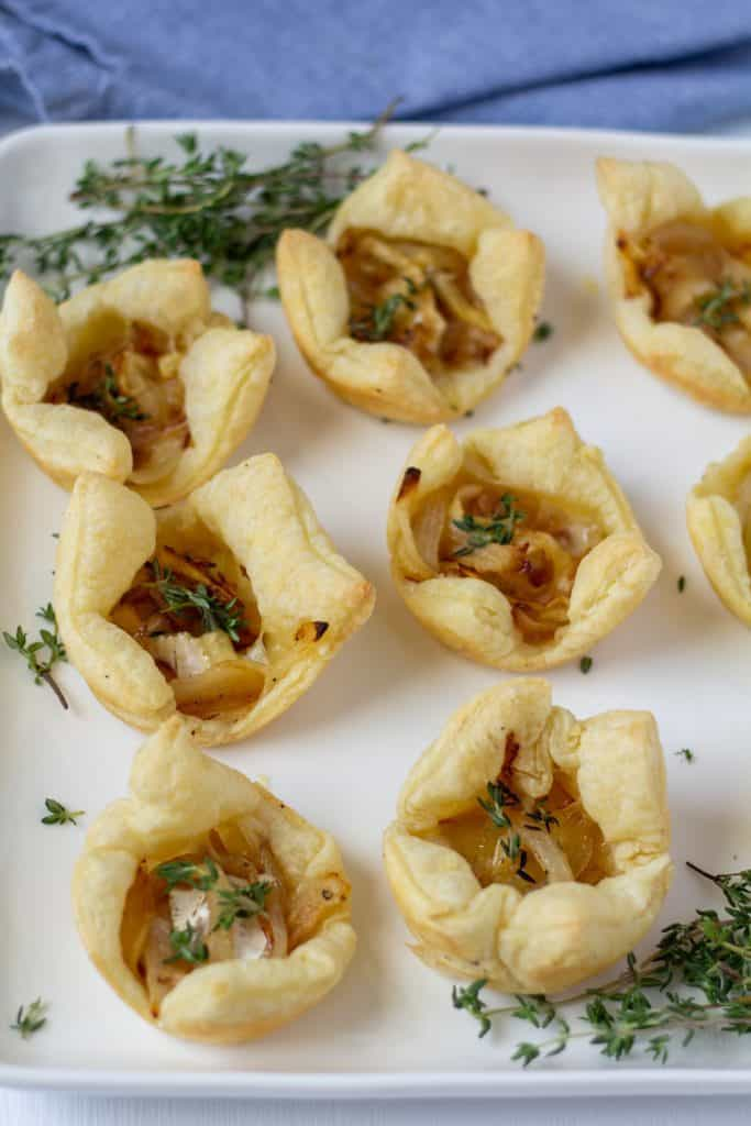 puff pasty bites on a white plate framed by thyme