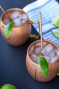 moscow mules in copper mugs on a black background with a white and blue striped napkin and sliced limes