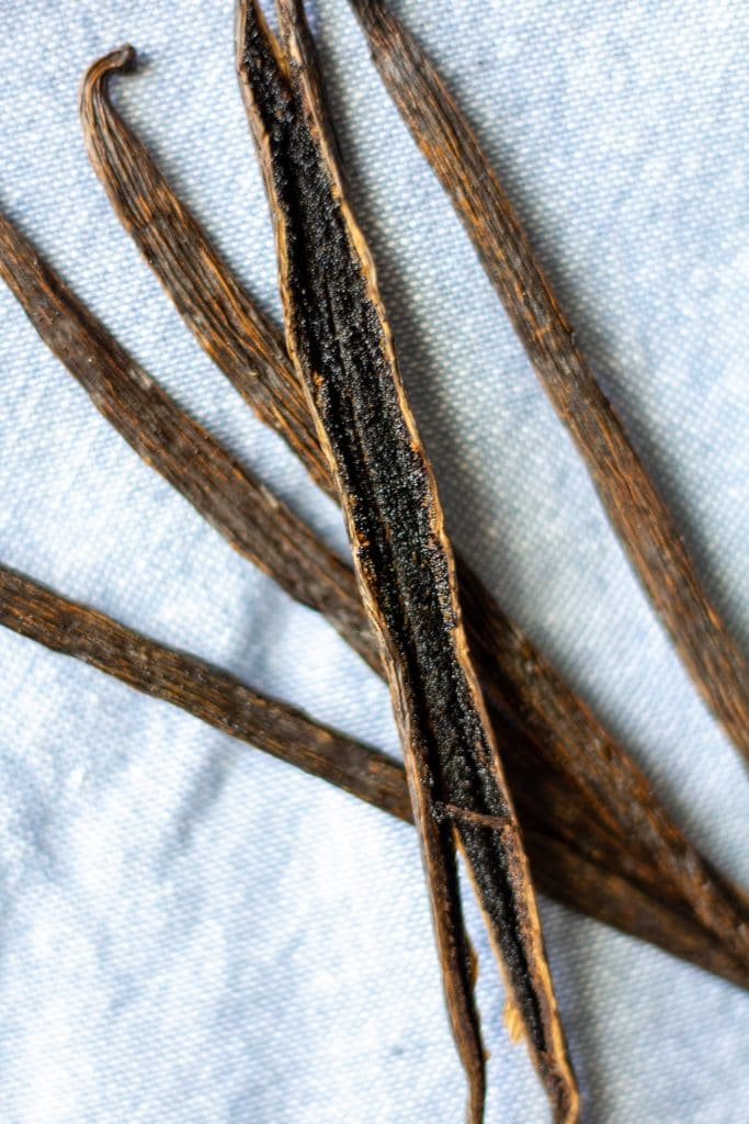 vanilla beans with one split open laying on a blue napkin