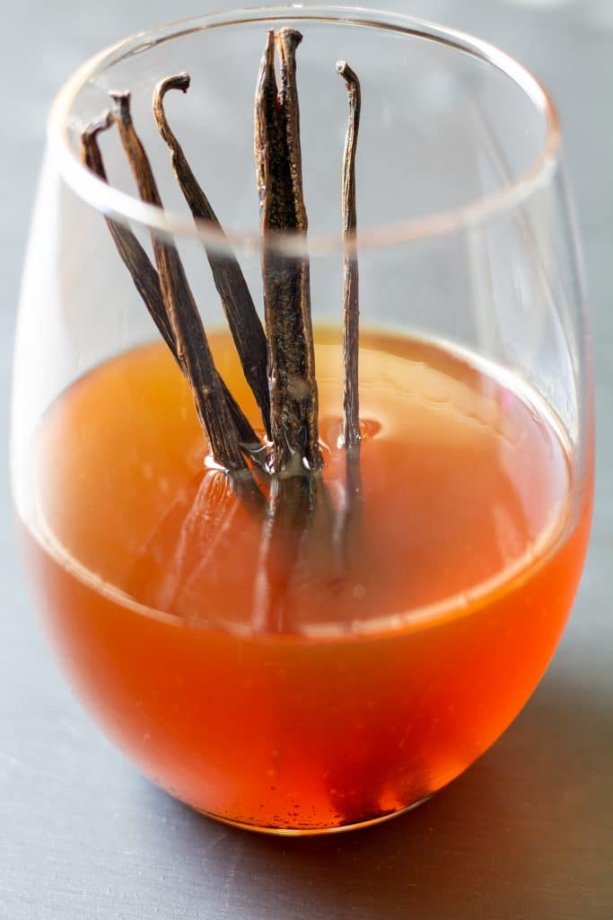 vanilla extract in a clear glass with vanilla beans standing up