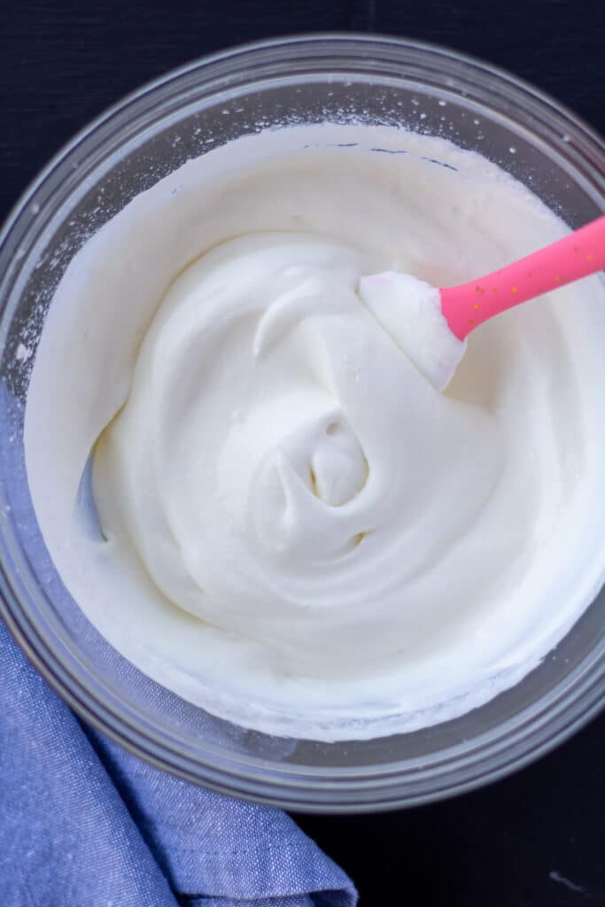 whipped cream in a glass bowl with a pink spoon on a black background