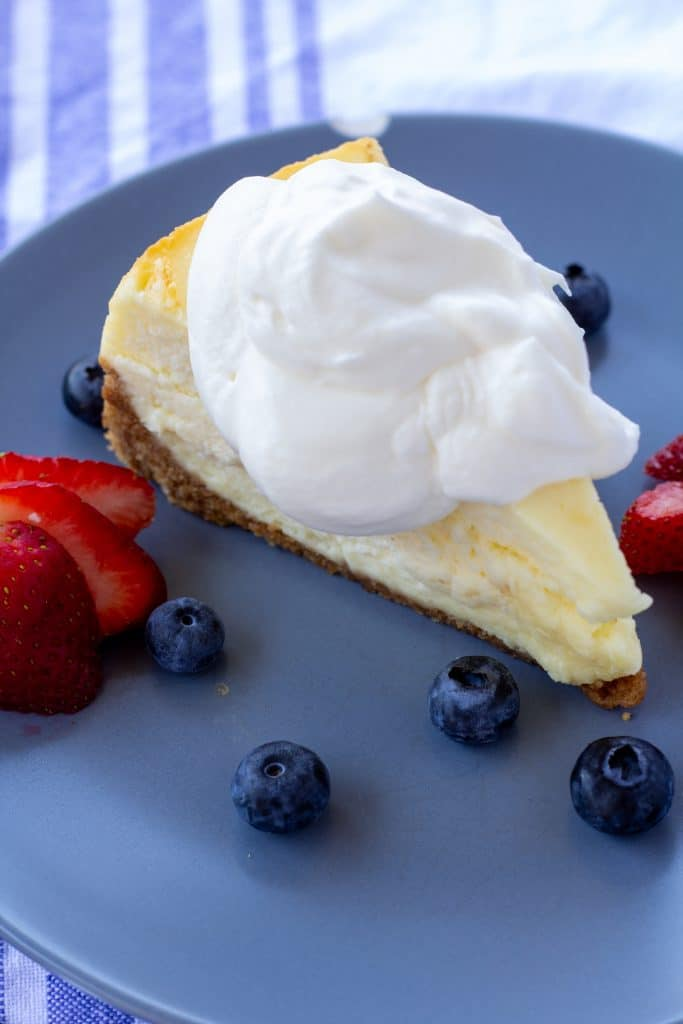 Whipped cream on a piece of cheesecake sitting on a blue plate with berries surrounding it