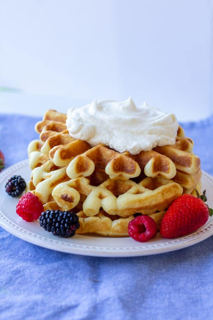 Breakfast waffles topped with whipped cream surrounded by berries on a white plate with a blue and white background.