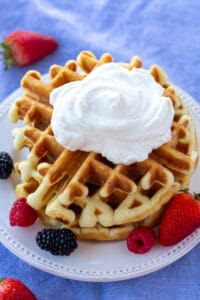 a stack of waffles with whipped cream, on a white plate, surrounded by berries