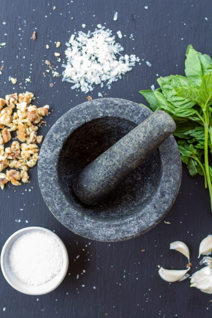 salt, parmesan, walnuts, basil, and garlic surrounding an empty mortar with a pestle in the middle