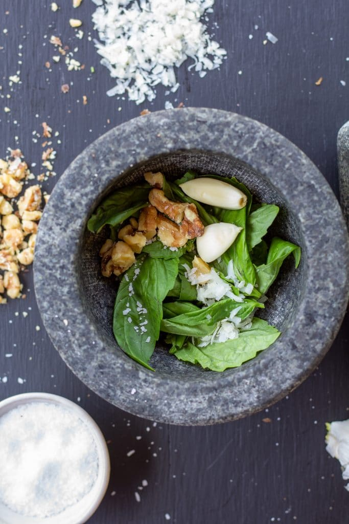 walnuts, garlic, salt, parmesan, and basil in a mortar on a black background