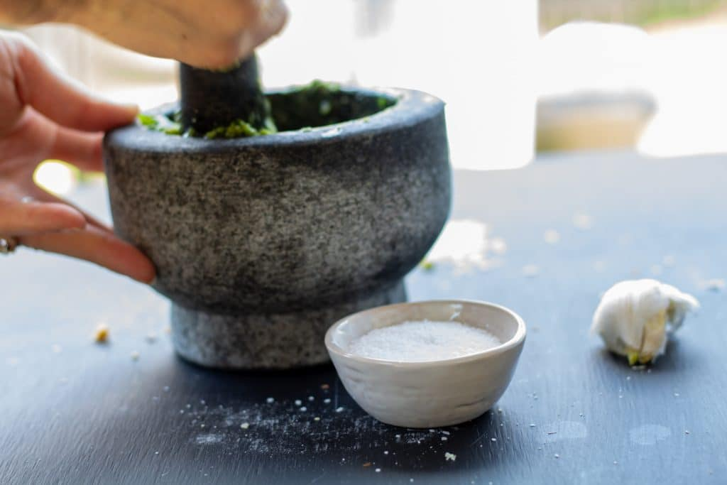 hands mixing with a mortar and pestle on a black background and a bowl of salt on the side