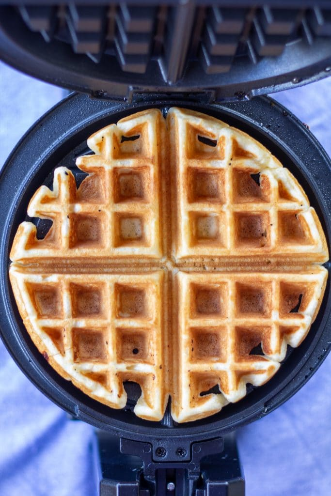 a waffle in an iron on a blue background