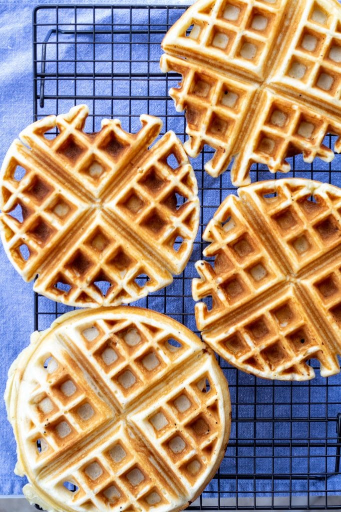 Waffles on a cooling rack with a blue background