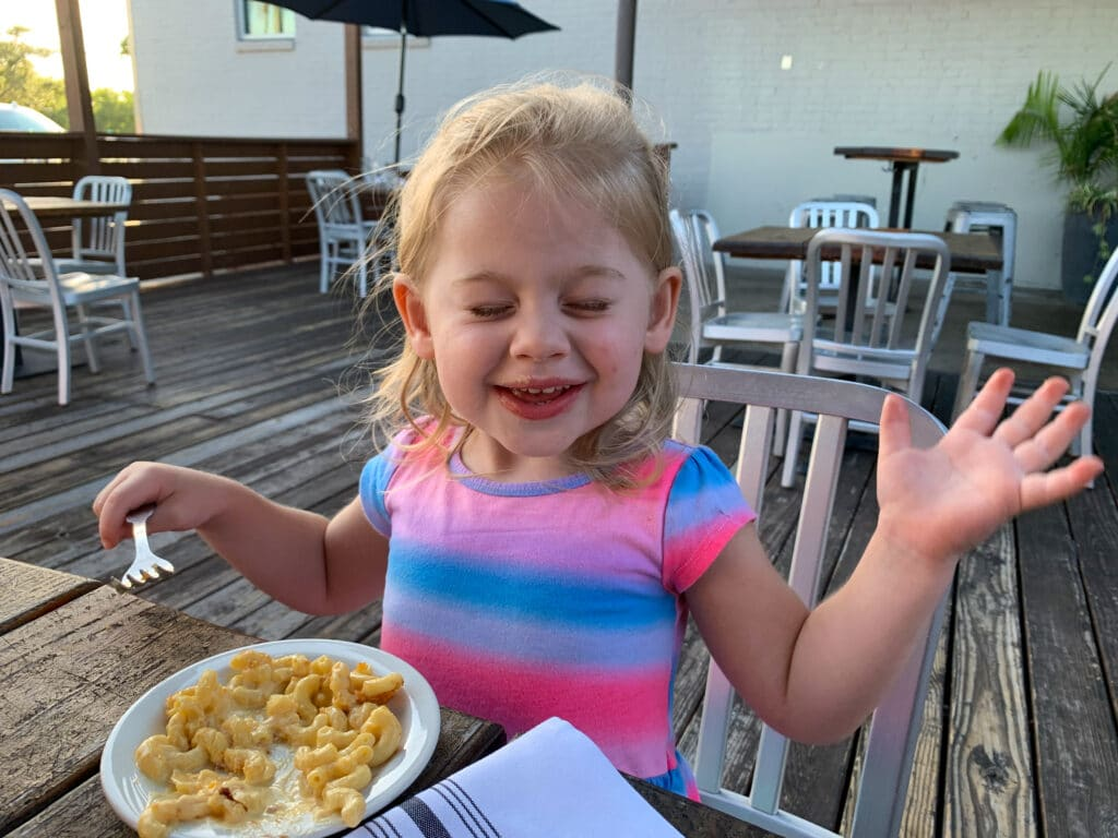 a little girl in a pink dress eating food outside