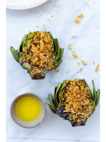 artichokes topped with a parmesan panko breading next to a side of butter on a white background