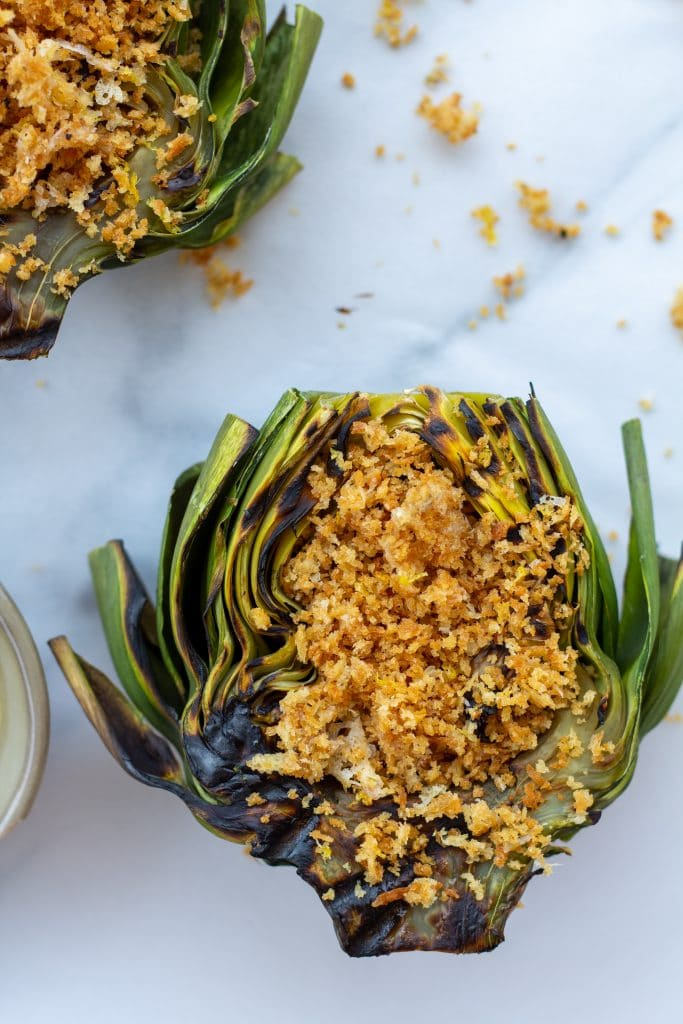 close up view of an artichoke with a parmesan panko topping
