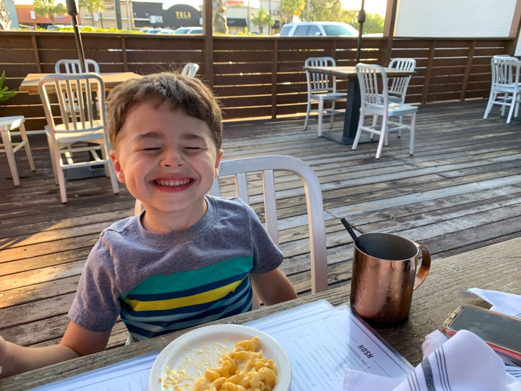 a little boy smiling at an outdoor lunch table