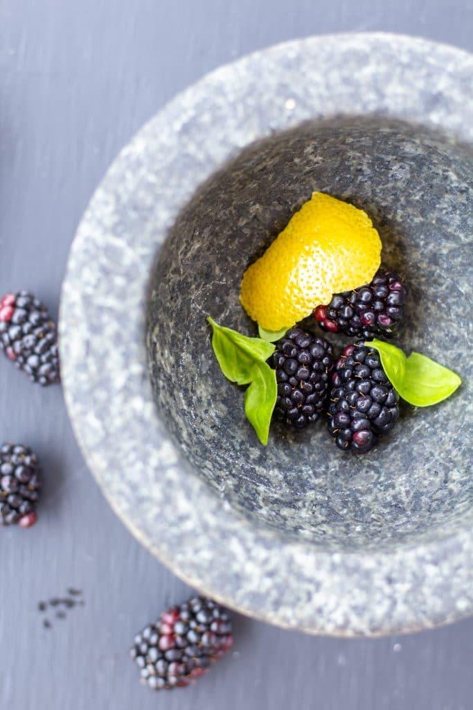 blackberries, lemon, basil in a mortar