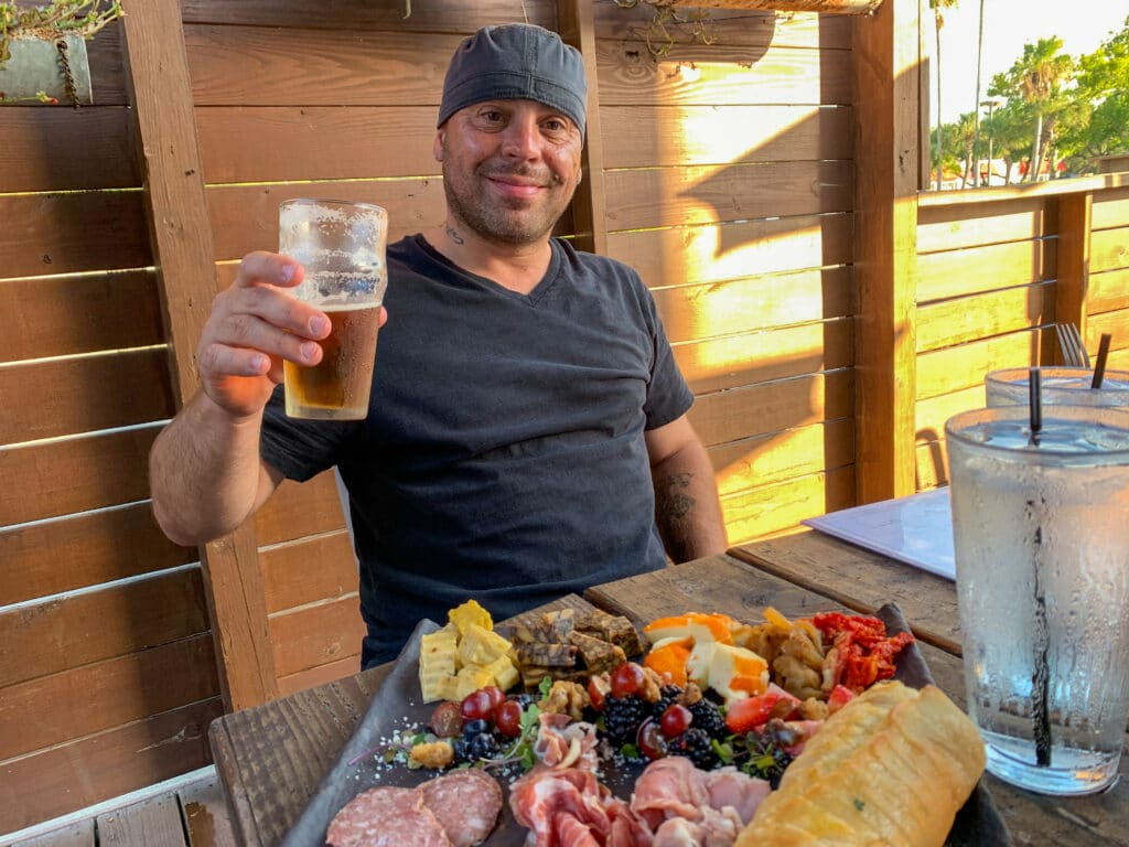 a man holding a beer at an outdoor table