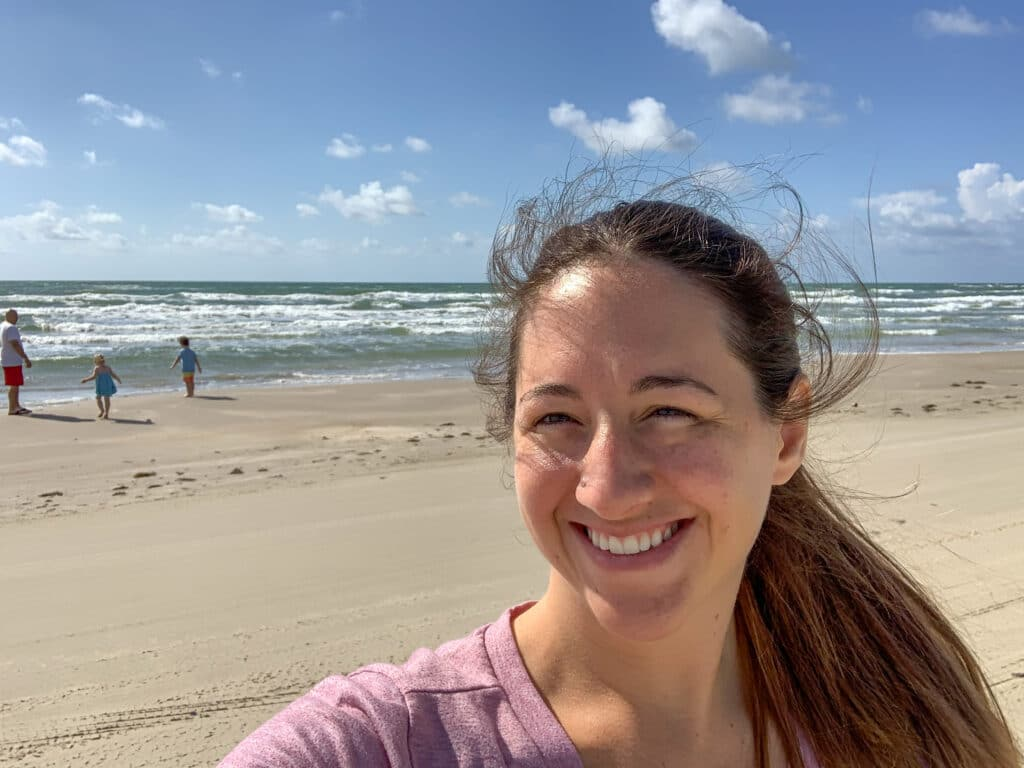 a woman smiling at the beach
