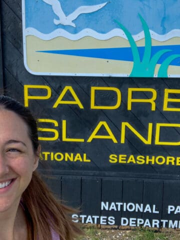 Padre Island sign with a woman taking a selfie