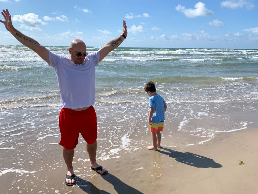 a man and little boy standing in the water at the beach
