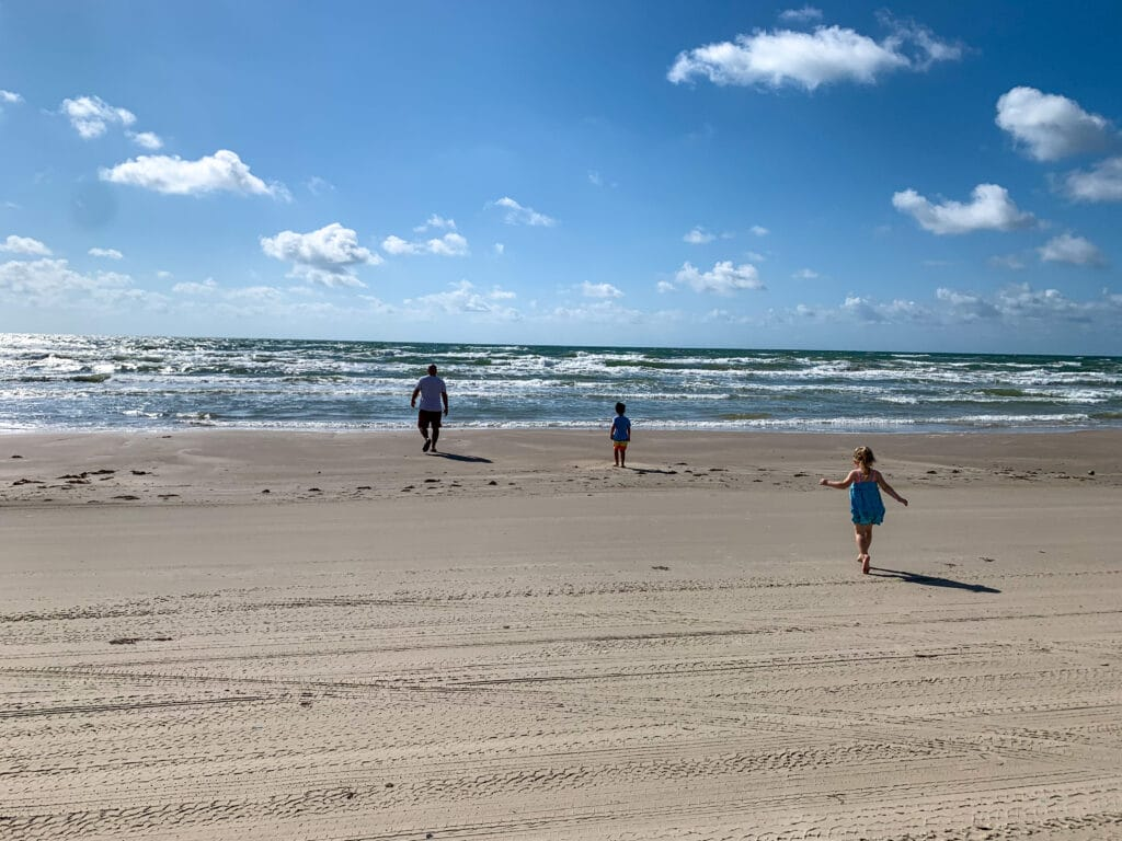 a man and two kids running toward the ocean on a beach