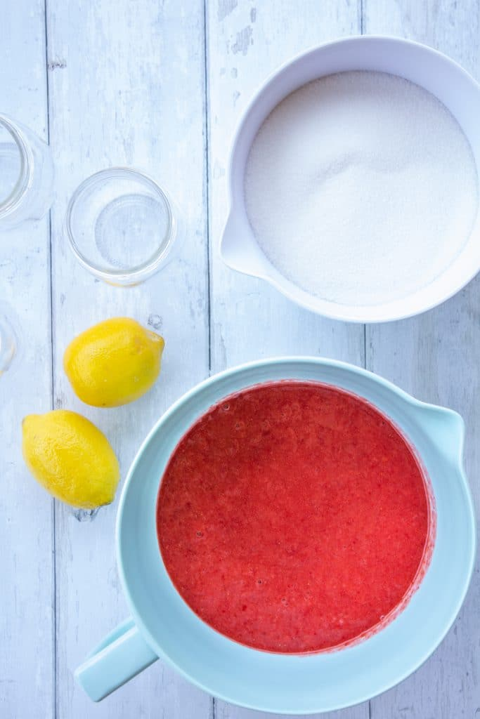 strawberries, sugar, lemons, and jars on a white background