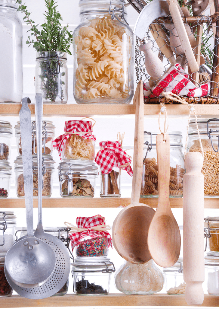 an organized pantry with jars of pasta, hanging spoons, and a jar of green leaves