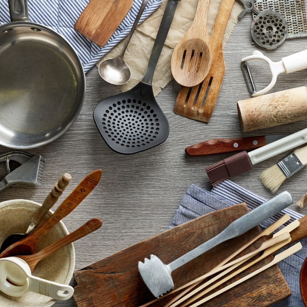 kitchen tools and utensils artfully arranged on a gray background