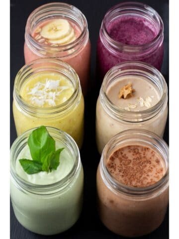 six smoothies lined up in a row on a black background