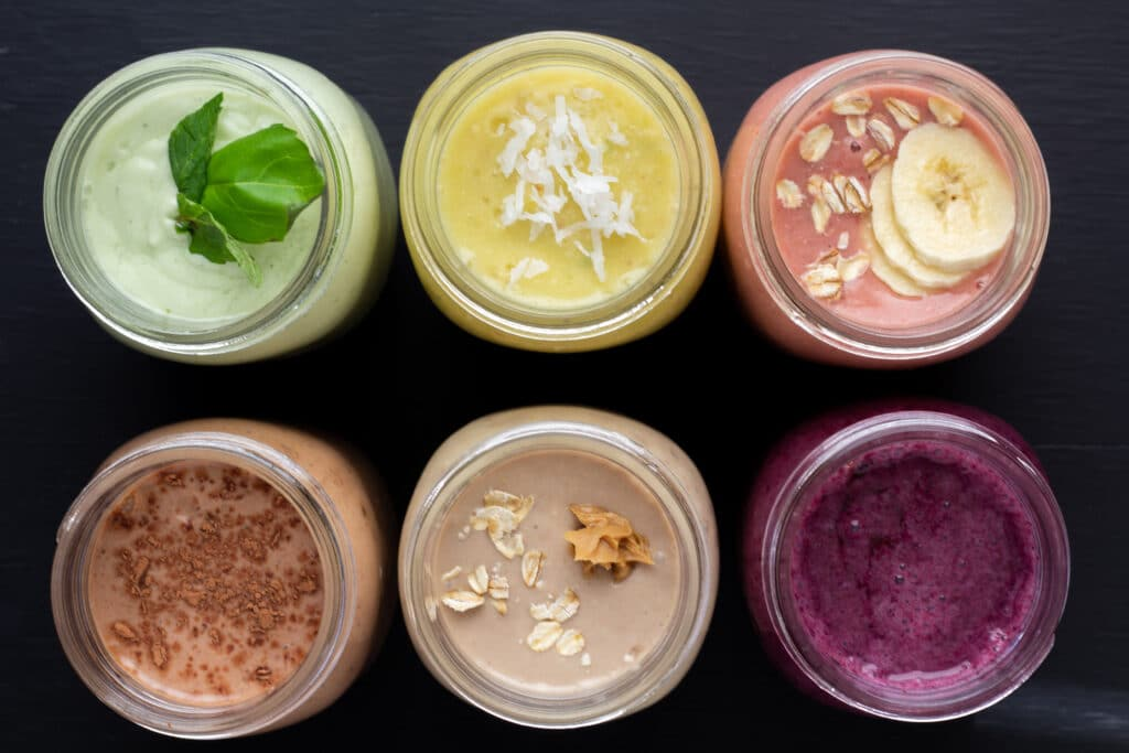overhead view of six smoothies lined up on a black background