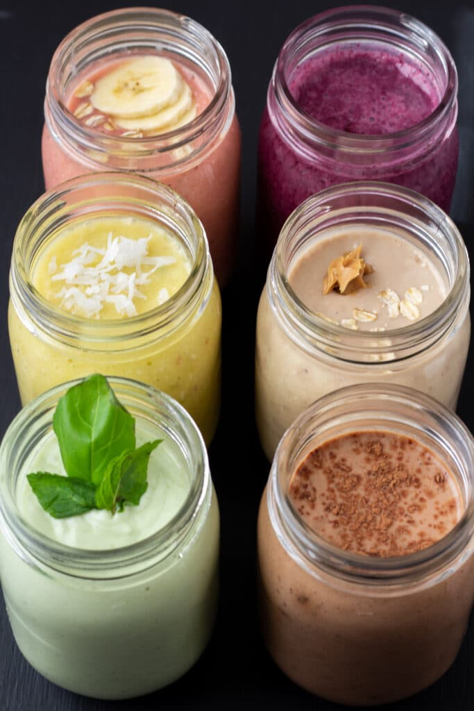 six easy breakfast smoothies lined up in a row on a black background