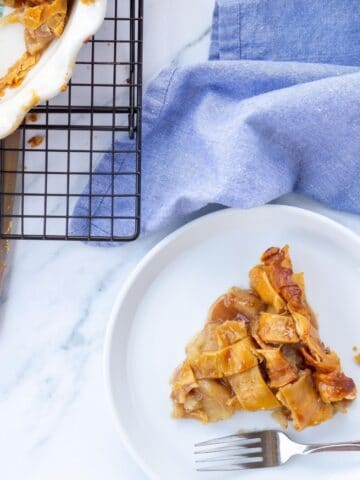 A slice of apple pie next to a cooling rack with a whole pie next to it